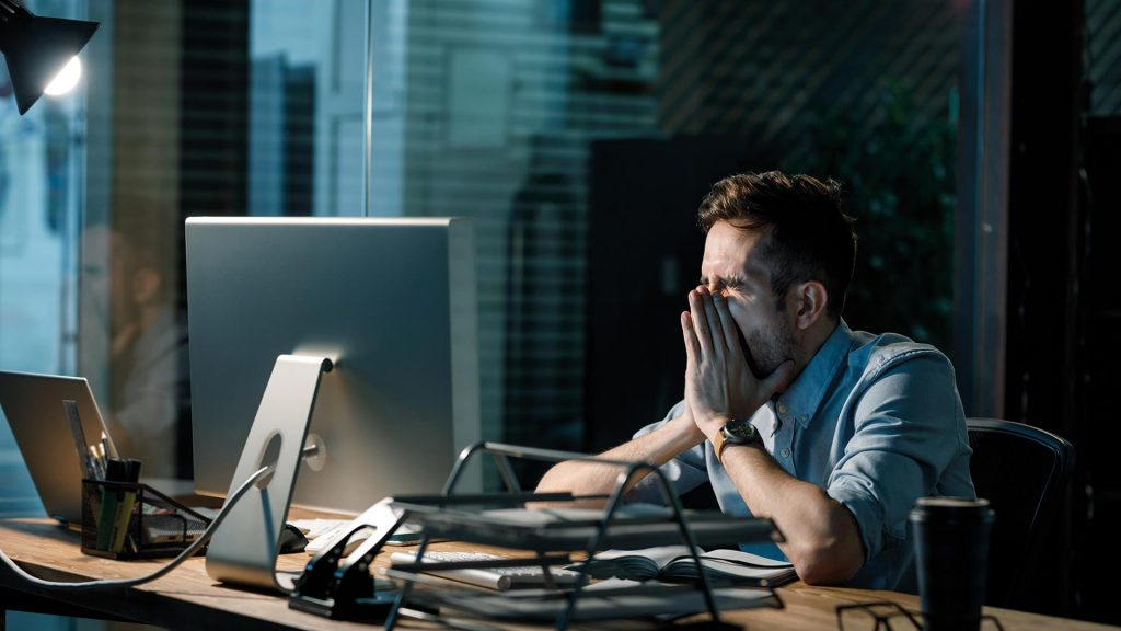 Man sitting ion front of a computer at a desk with his head in his hands